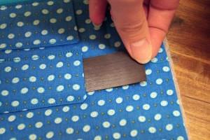 In jede der Taschen einen Magentstreifen schieben.