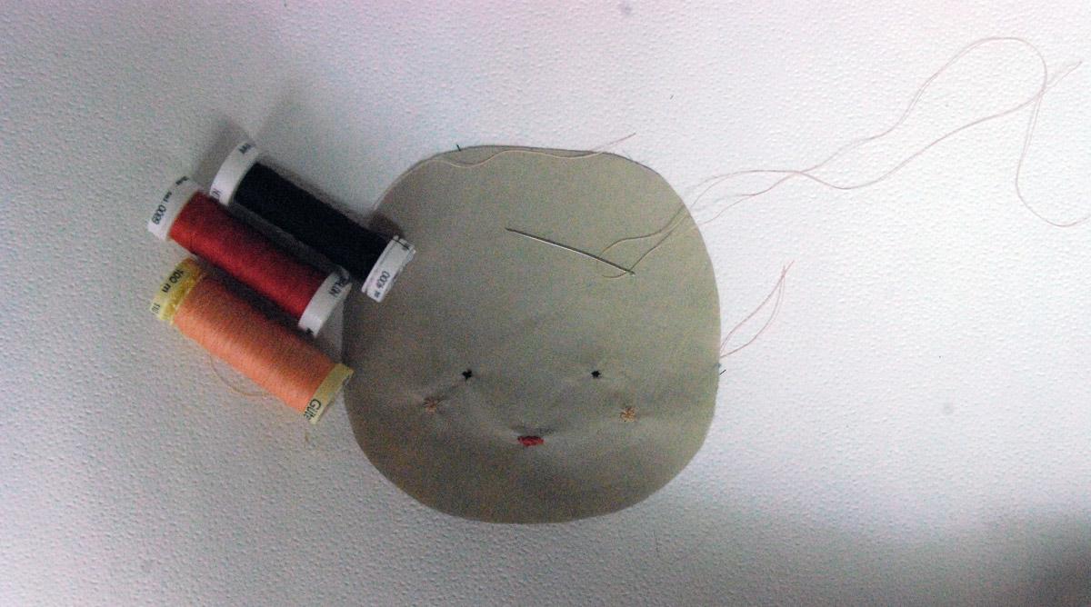 Bild3 - Nachdem die 3 Flieseinlagen auf Gesicht und Oberkörper aufgebügelt wurden, geht es ans Sticken von Augen, Mund und Punkte-Bäckchen.